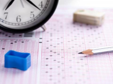 Pencil and clock over Scantron testing sheet